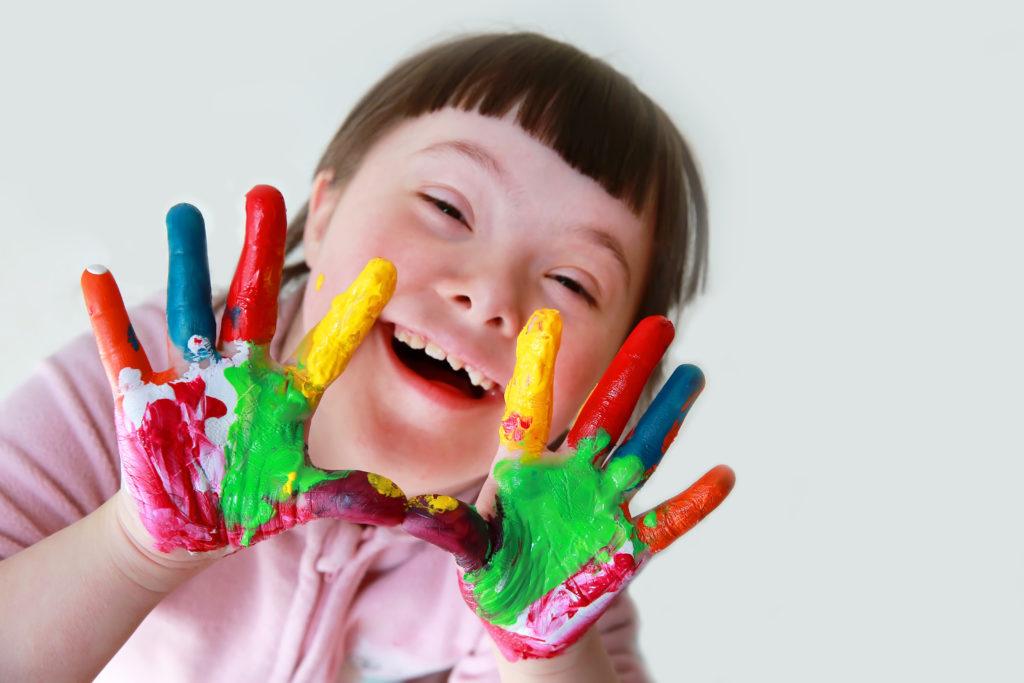 Glad jente med Downs syndrom som har mange ulike farger malt på hendene.