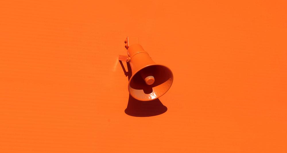 En megafon på oransje bakgrunn, symbol fo r de viktige stemmene,