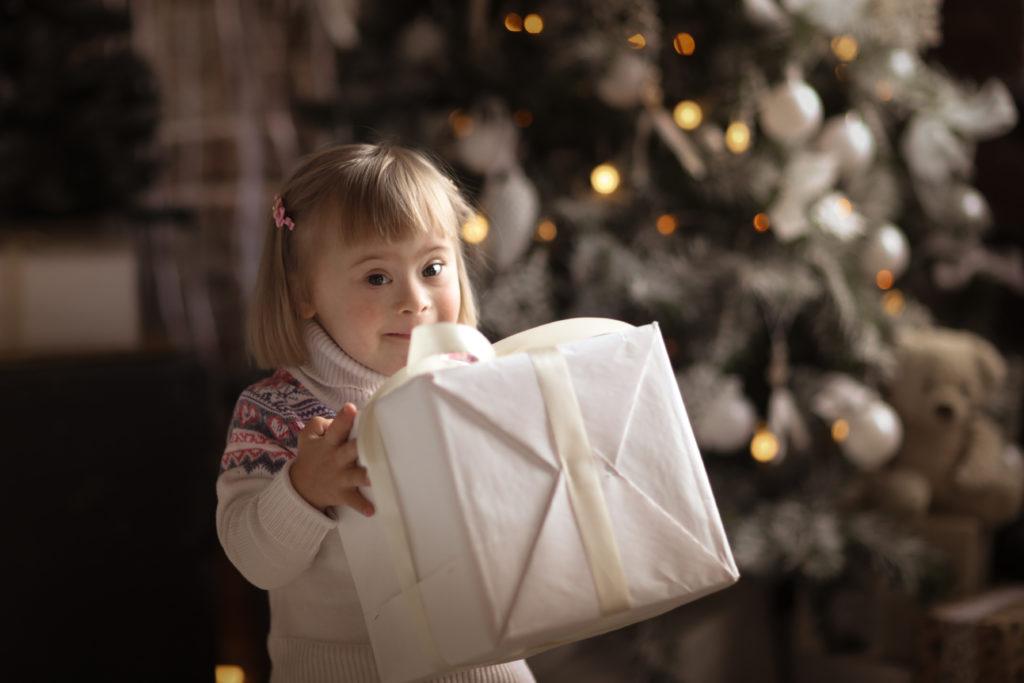 Liten jente med Downs syndrom holder en stor pakke. Vi deler historier frem mot jul.