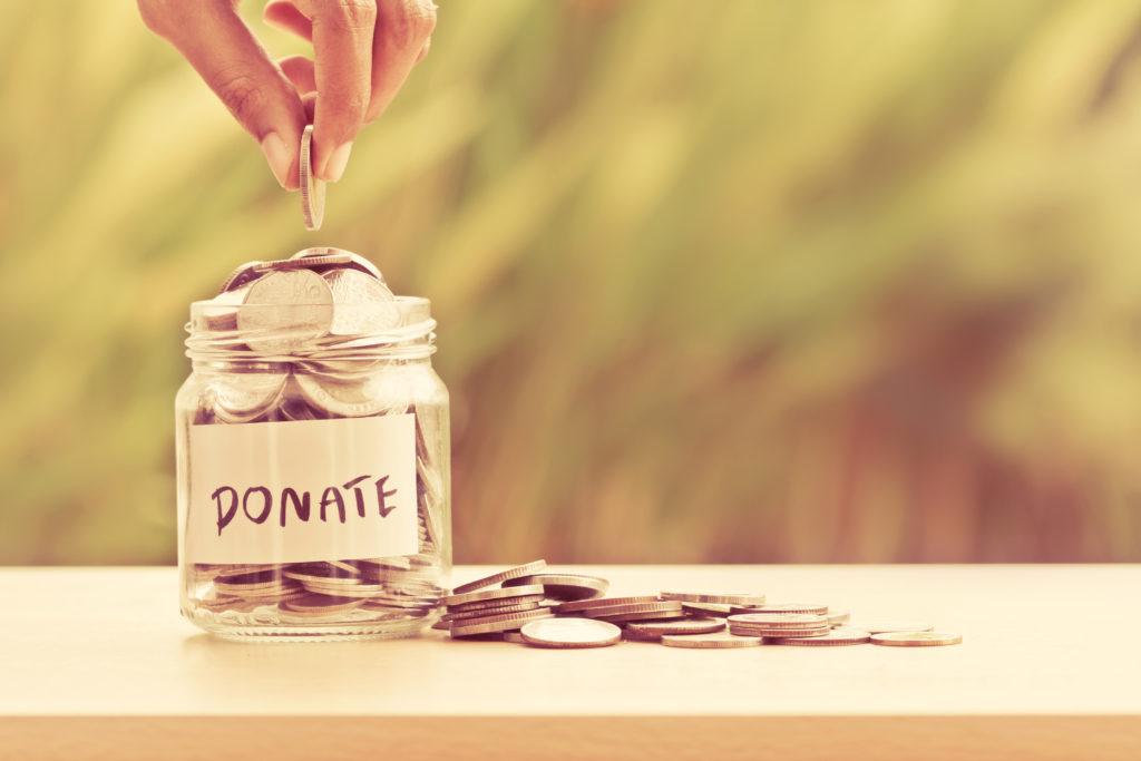 Donasjons-krukke full av mynter