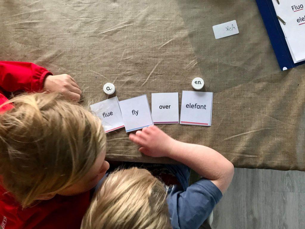 Ask øver på ord ved hjelp av kort med ord på og en storebror som hjelper til.