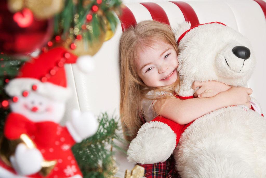 Jente med Downs syndrom koser på en stor bamse i julemiljø.