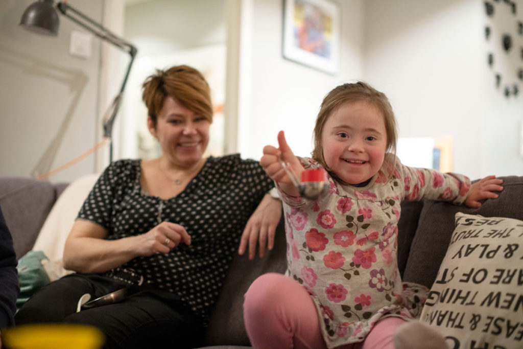 Liten jente  med Downs syndrom viser frem gele på skje til fotografen. Stella sammen med mamma Lene Lindquist