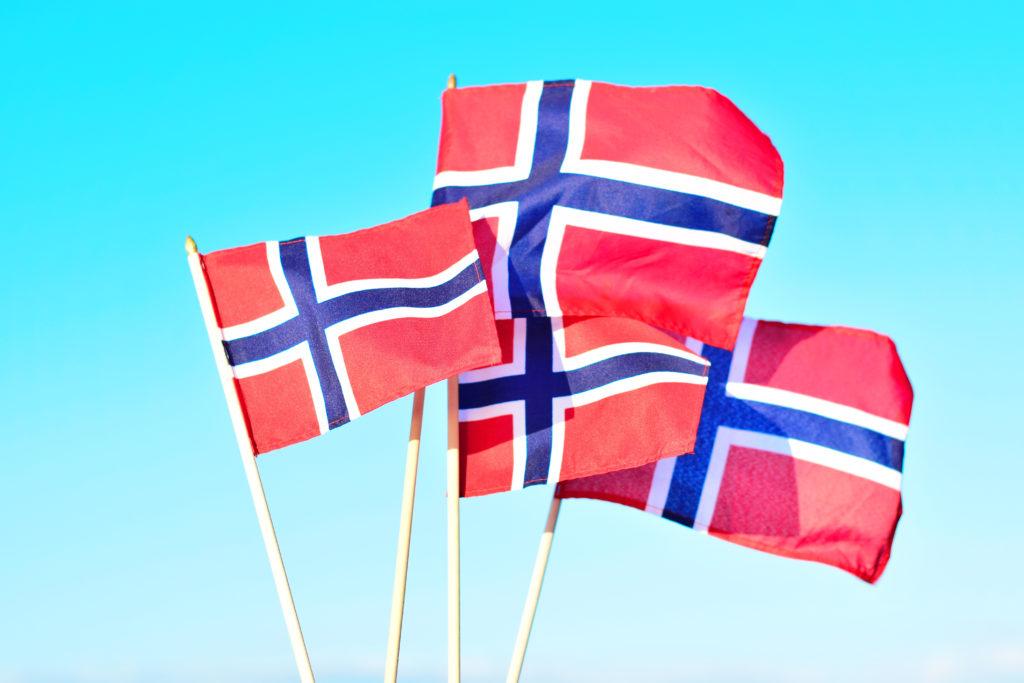 Tre norske flagg veiver i vinden med lys blå himmel bak.