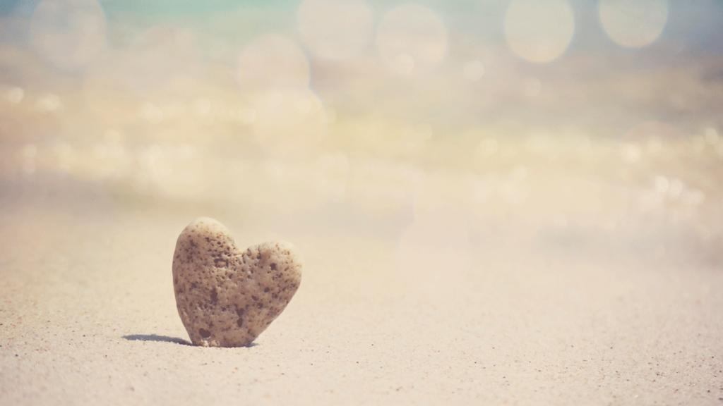 En stein formet som et hjerte med sandtrand i bakgrunn