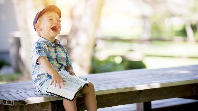 Liten gutt ler høyt av en bok
