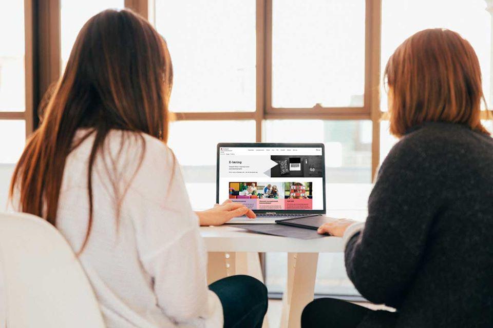 to damer ser på statped sine nettsider på en skjerm
