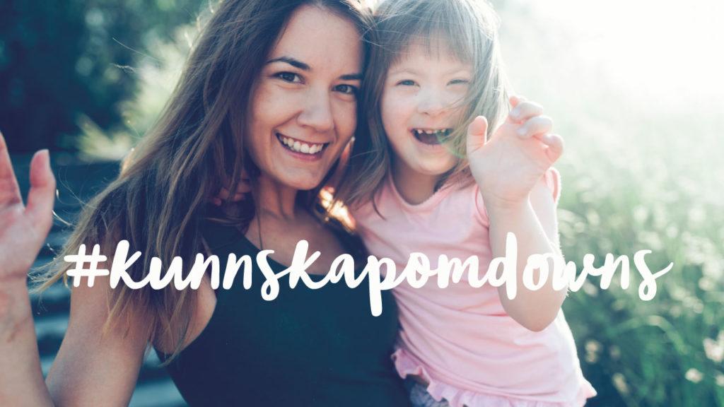 Mor holder datter med Downs syndrom i armene og de smiler til kameraet