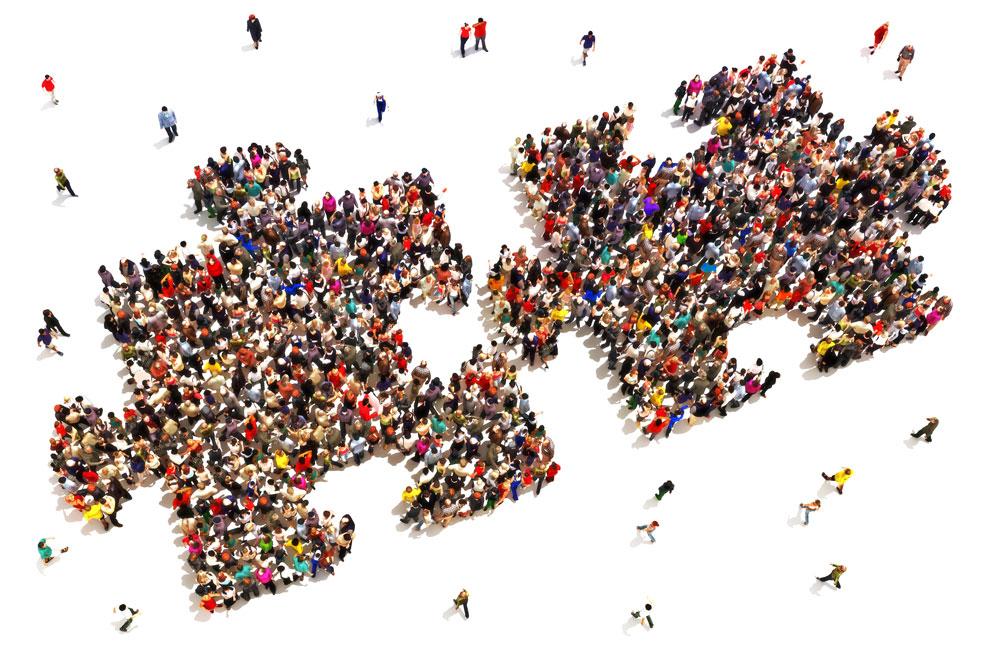 Folk setter bitene sammen konseptet. Stor gruppe mennesker i form av to puslespillbrikker på en hvit bakgrunn.