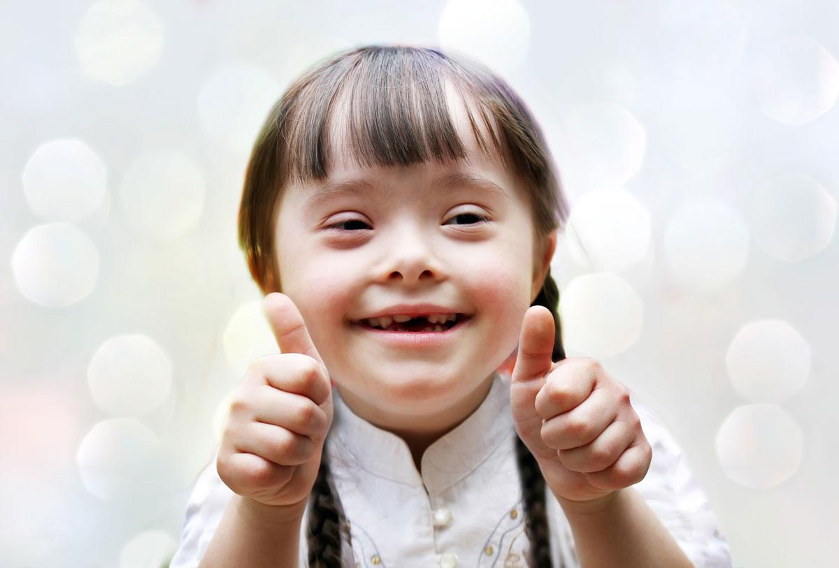 Foto av liten jente med downs som smiler og viser to tomler opp